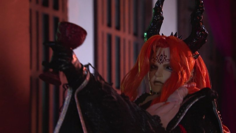 redheaded demon puppet from Thunderbolt Fantasy lifting a goblet of wine