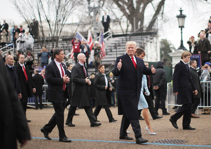U.S. President Donald Trump gestures while walking with wife Melania and son Barron during the Inaugural Parade in Washington, January 20, 2017. Donald Trump was sworn in earlier as the 45th President of the United States. (Carlos Barria/Reuters)