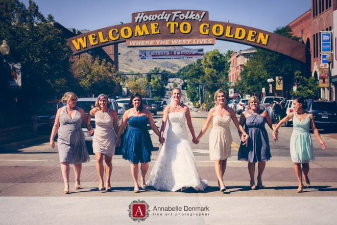 The bride and her bridesmaids are walking on the road, under the Golden sign