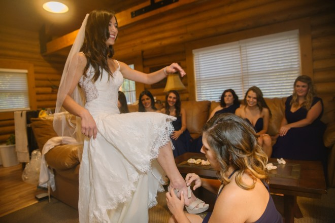 Maid of honor helps with bridal shoes