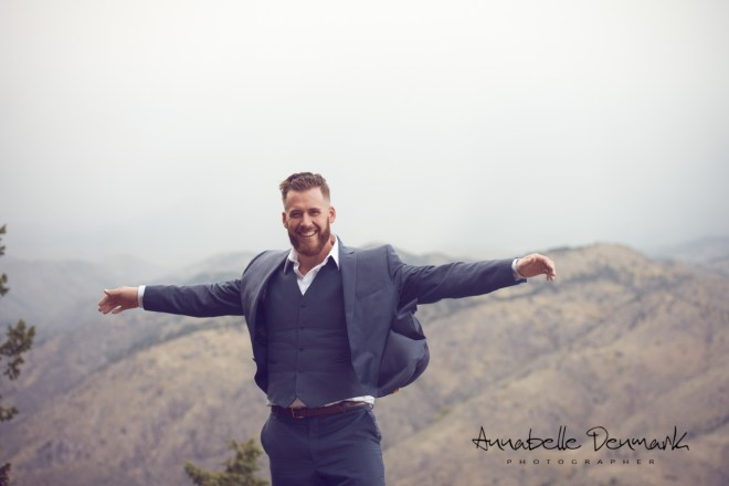 man extending arms in front of overlook