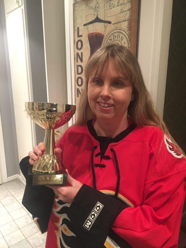 Anna på foto iklädd hockeytröja med vinnarpokalen för Annas Championship.