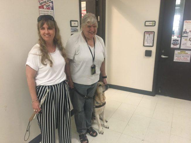 Foto på Anna tillsammans med Ann och hennes ledarhund i korridoren på the Windward community Colege.