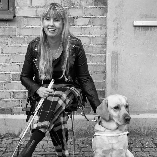Me sitting next to my guide dog, a light labrador wearing a white harness.