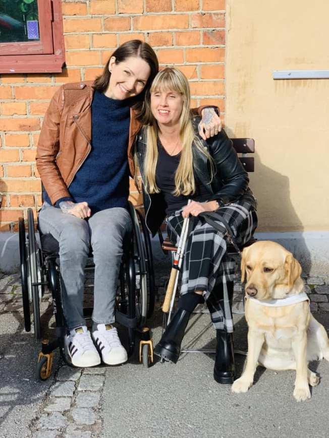 Yasmin Nilson tillsammans Med Anna Bergholtz sitter ute intill varandra. Bredvid Anna har hon sin ledarhund sittandes till höger i bild.