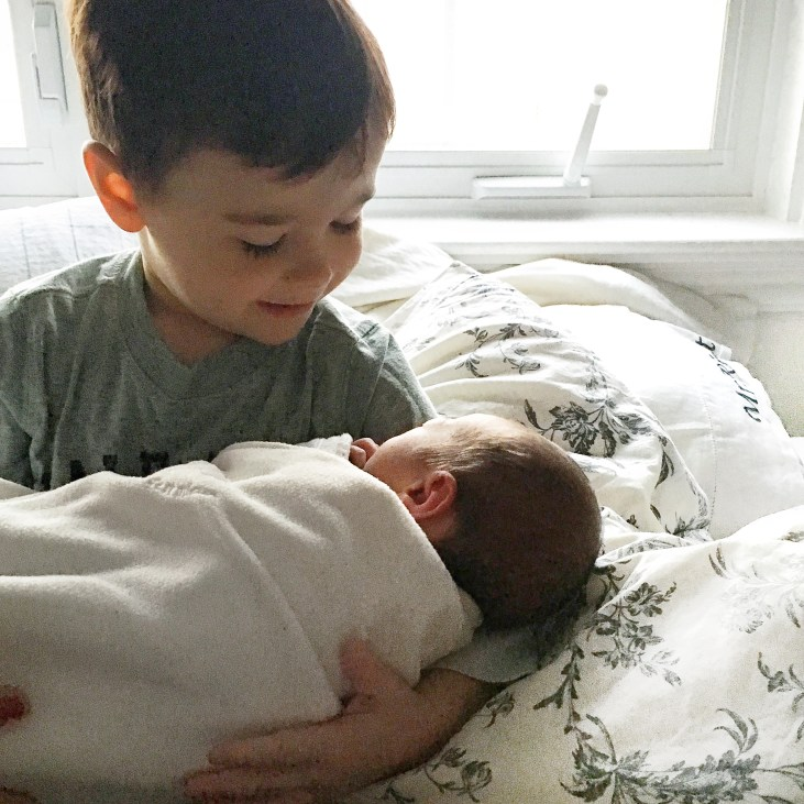 a fair skinned 4 year old boy holds and looks at his 2 day old fair skinned baby sister