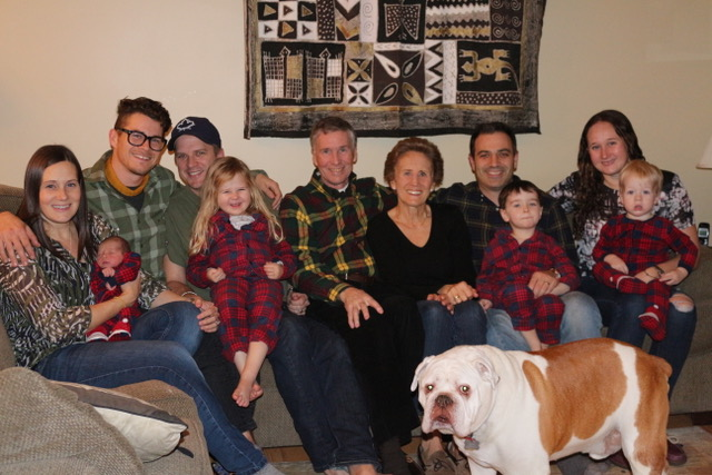 a fair skinned family sits on a couch with the grandparents sitting in the middle of the group, the 4 little kids wear matching red and blue plaid chrismas pajamas and sit on their parents laps