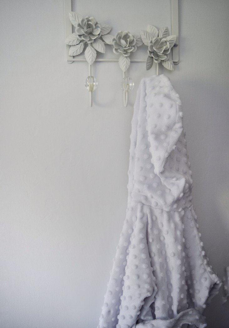 a pretty floral coat rack with three hooks hanging over the closet door in the baby nursery with a white baby bath robe hanging on one of the hooks
