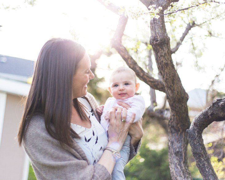 a Toronto photographer took this photograph of me holding my 5 month old baby girl and smiling at her, the sun shines through the plum trees in the background