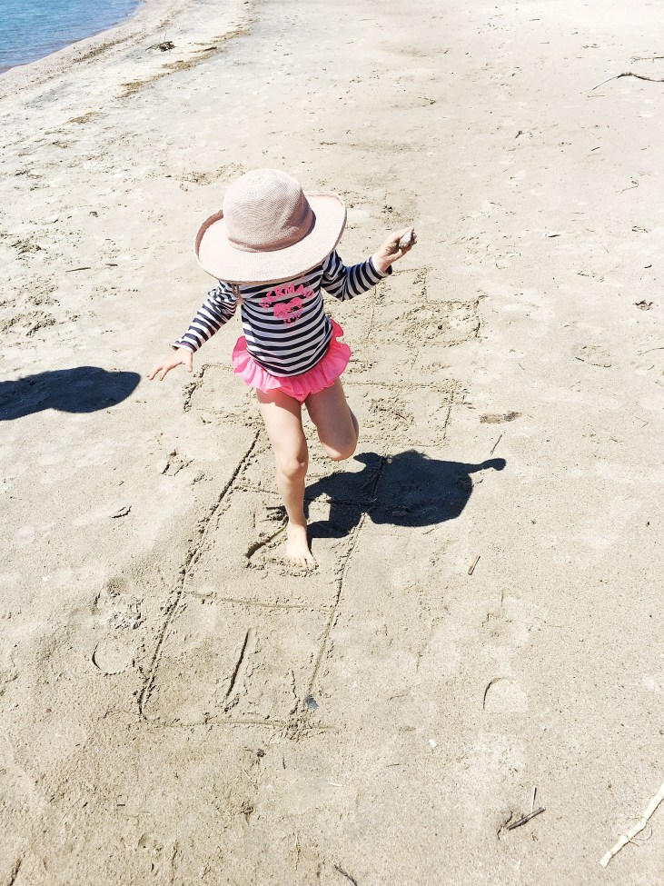 a light skinned 4 year old girl playing hopscotch on a beach- beach activities