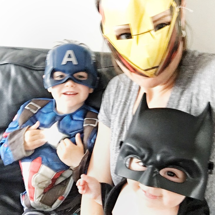 a 4 year old boy, a 6 month old girl and a mom all wearing various superhero masks and smiling at the camera