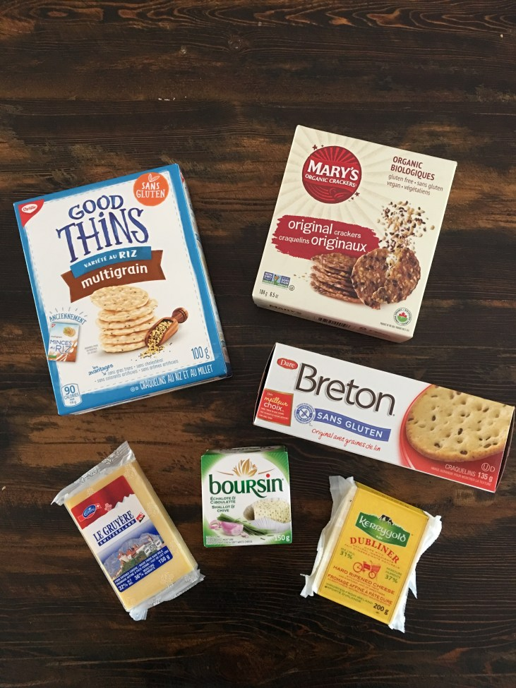 flat lay of gluten free crackers and cheese (rice crackers, mary's crackers, and breton gluten free crackers)