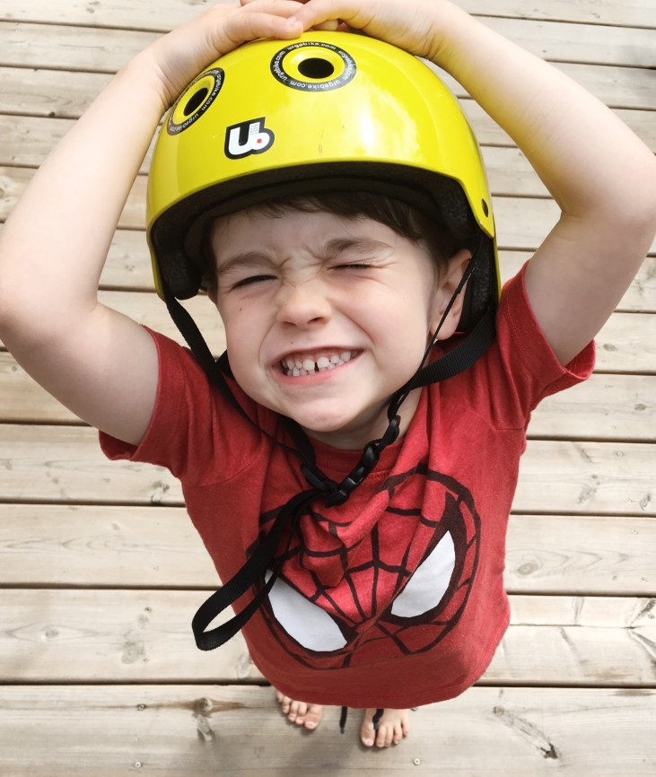 4 year old boy wearing a yellow bike helmet and smiling