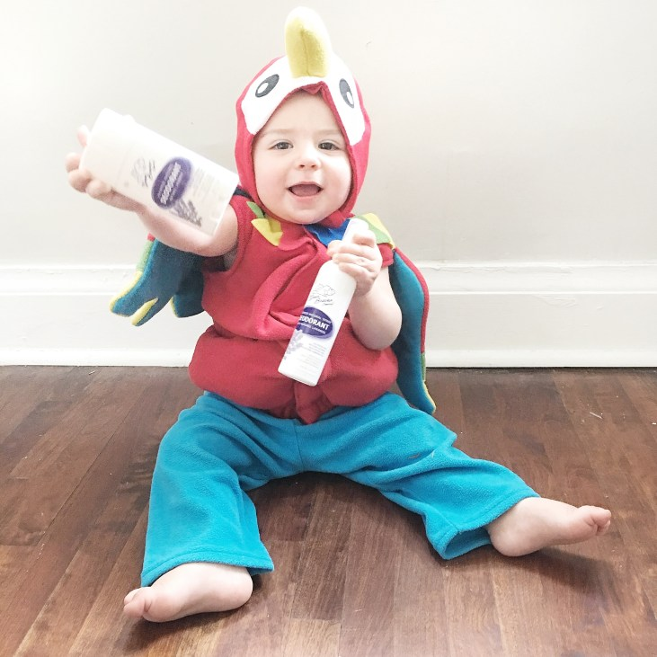 baby girl dressed as parrot holding natural deodorant