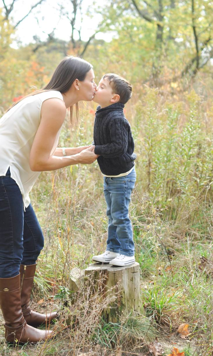 mom kissing 4 year old son standing on a tress stump in a fall family photoshoot