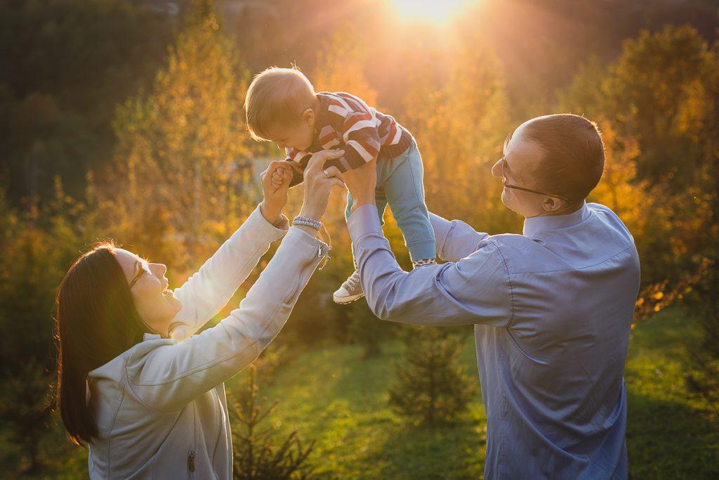 rodzice z dzieckiem o zachodzie słońca