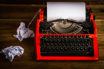 Typewriter with crumpled sheets. On wooden background.