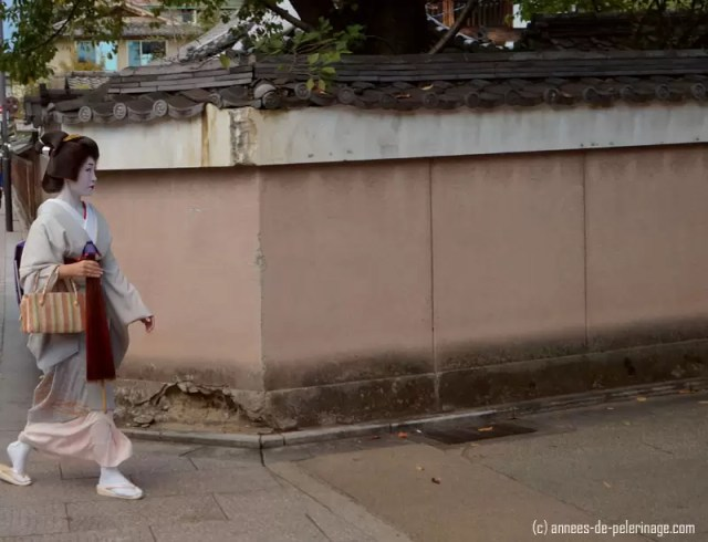 geisha (meiko) passing around a corner in gion, kyoto