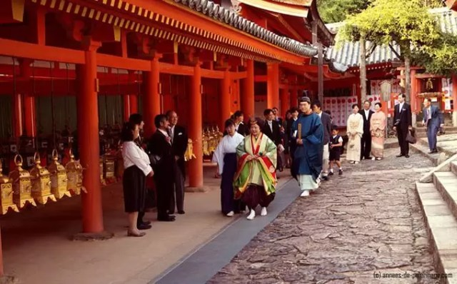A wedding couple dressed like a japanese court noble woman from the Nara period wearing a junihitoe at Kasuga-Taisha in Nara
