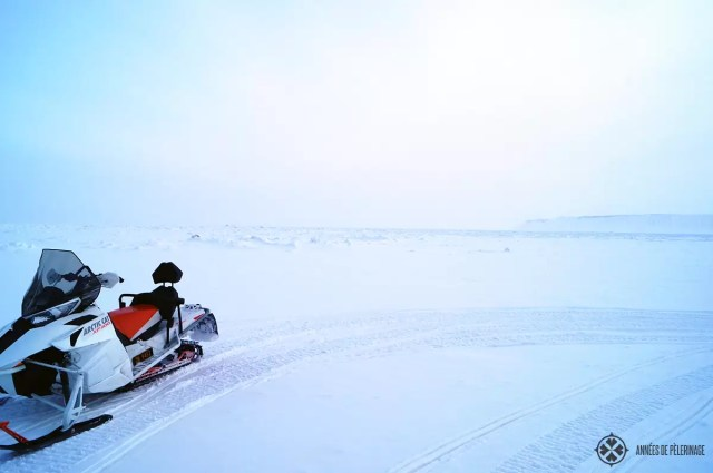 A snow mobile standing at the border to the endless pack ice on spitsbergen