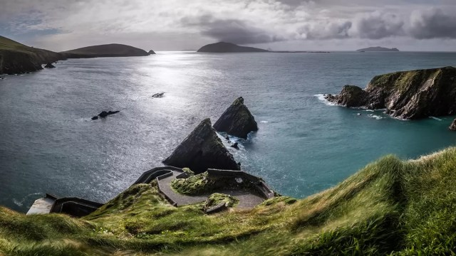 Dunquin harbour with a meandering road and the coast
