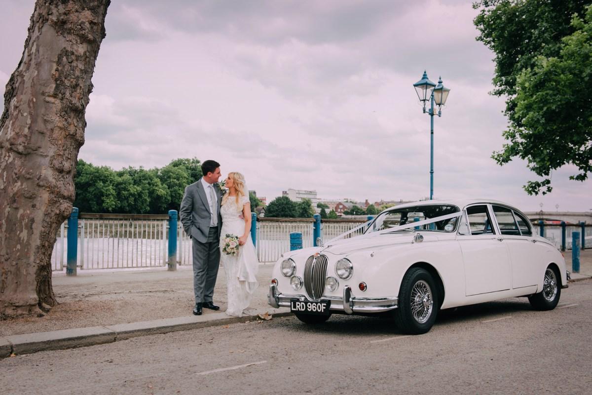 bride and groom on london putney embankment with vintage wedding car