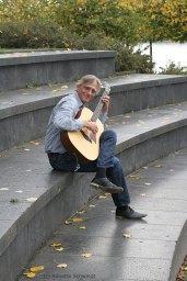 Christian Straube sitzt im Amphitheater und spielt Gitarre