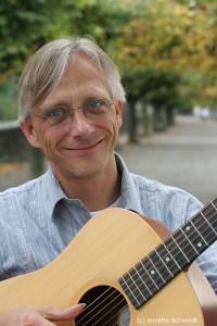 Christian Straube mit Gitarre und der der Beueler RHeinpromenade in Hintegrund