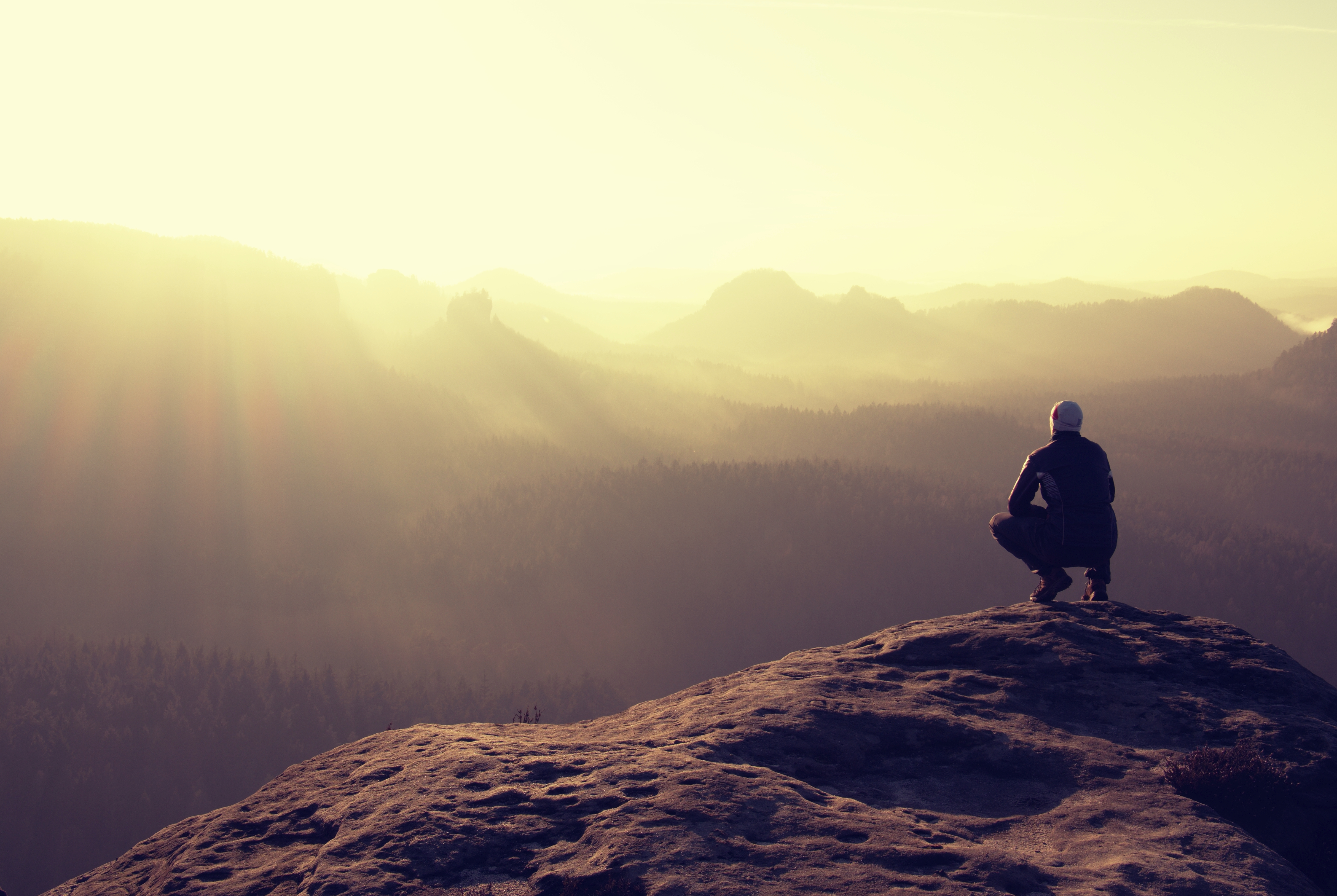 Hiker sits on a rocky peak and enjoy the mountains scenery - Annette Sloly Hypnotherapy