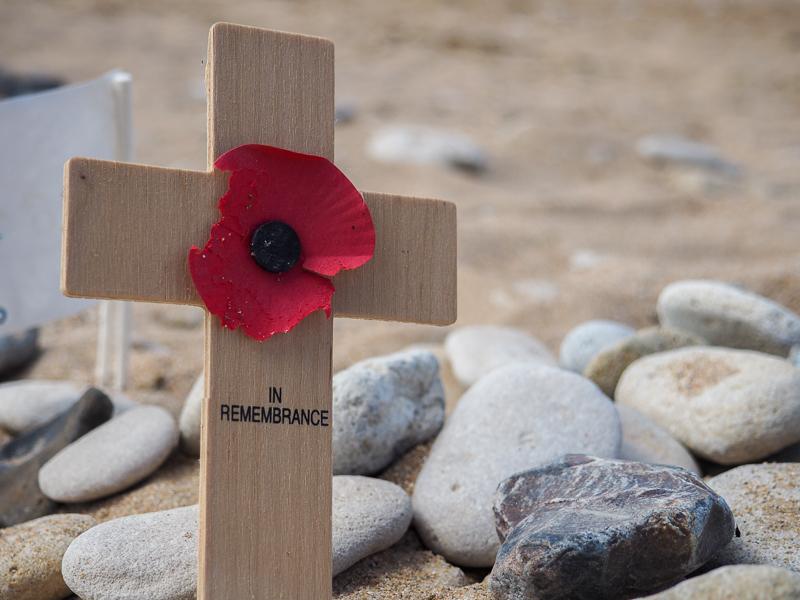 Petite croix de bois marquée d'un coquelicot sur une plage de Normandie.