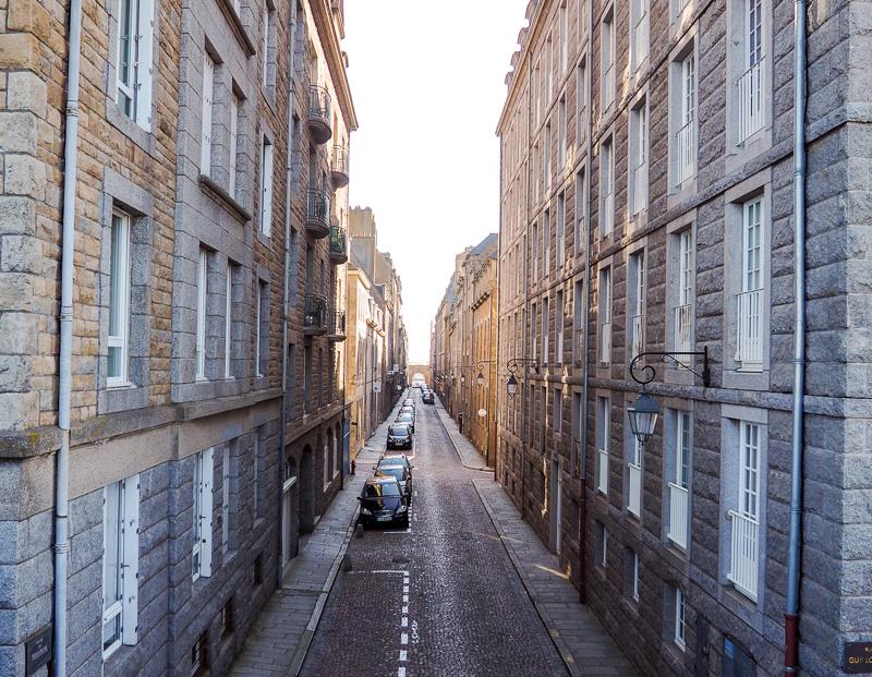 Rue pavée de la ville de Saint-Malo, bordée de bâtiments de pierres grises