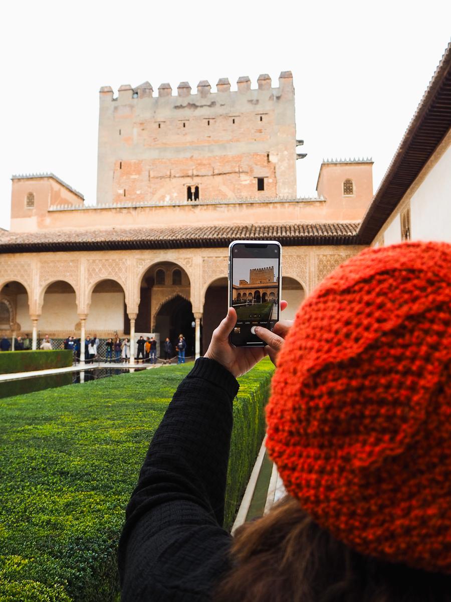 Femme prenant en photo l'Alhambra de Grenade