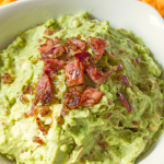 Bacon and Roasted Garlic Guacamole | Annie's Noms - This is no normal guacamole! This mind-blowing homemade guacamole has roasted garlic, bacon and fried onions in! Served with tortilla chips, this will be one appetizer you won't want to share!