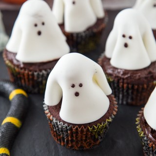 A chocolate frosted cupcake with a fondant ghost atop it; these Ghost Cupcakes are treats that adults and kids alike will love! #ad