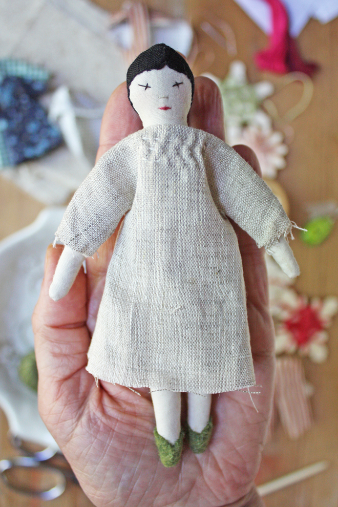 tiny rag doll with smocking detail on her dress