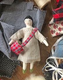 tiny cotton doll with a satchel and linen smock