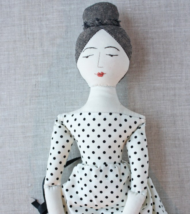 rag doll in an ivory and black polka dot dress