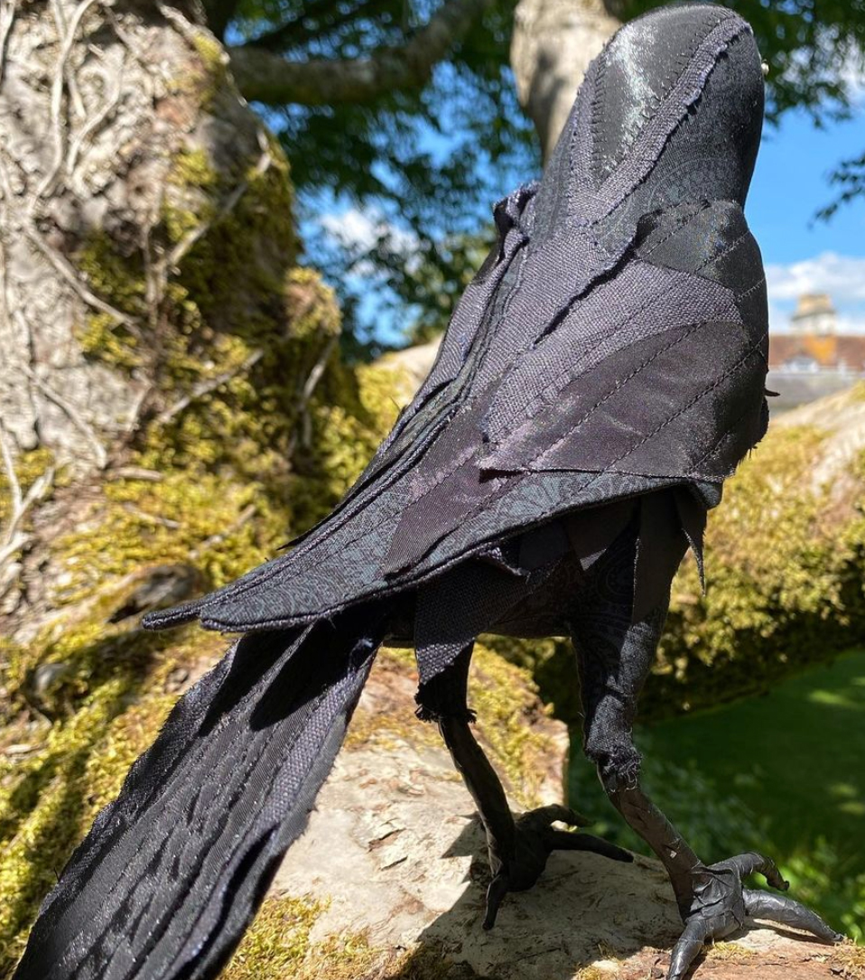 textile crow posed in tree