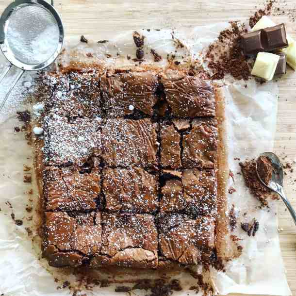 Chocolate brownies, sieve and chocolate on chopping board