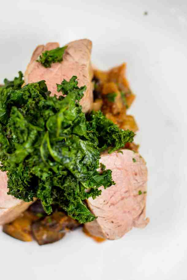 Pork tenderloin, spiced eggplant & crispy kale on white plate