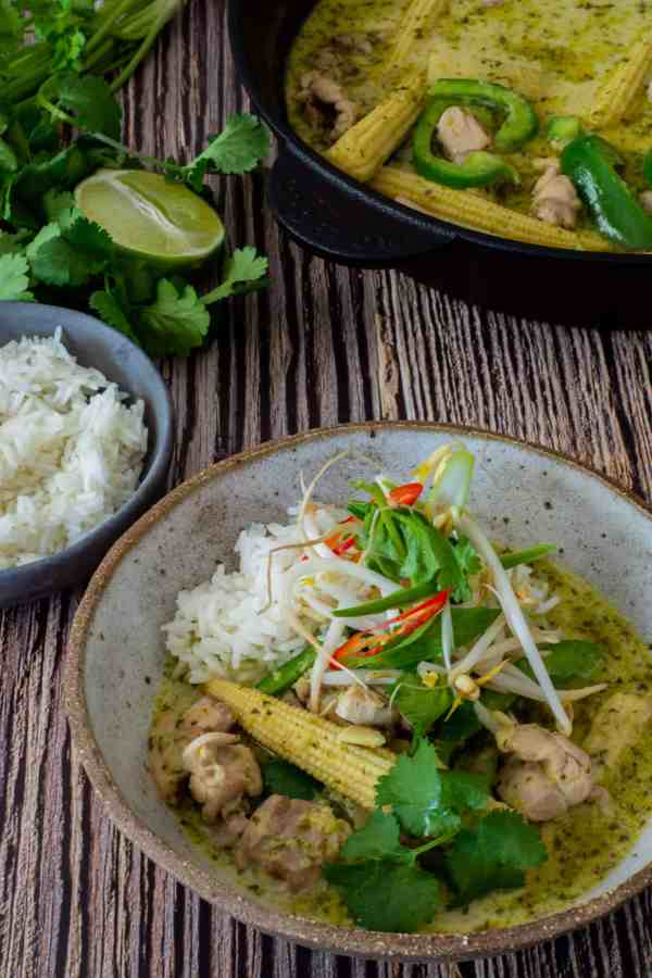 thai green curry, rice, herbs & lime on a table