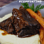 mushroom braised short ribs, cauliflower puree & carrots in a bowl on wooden table
