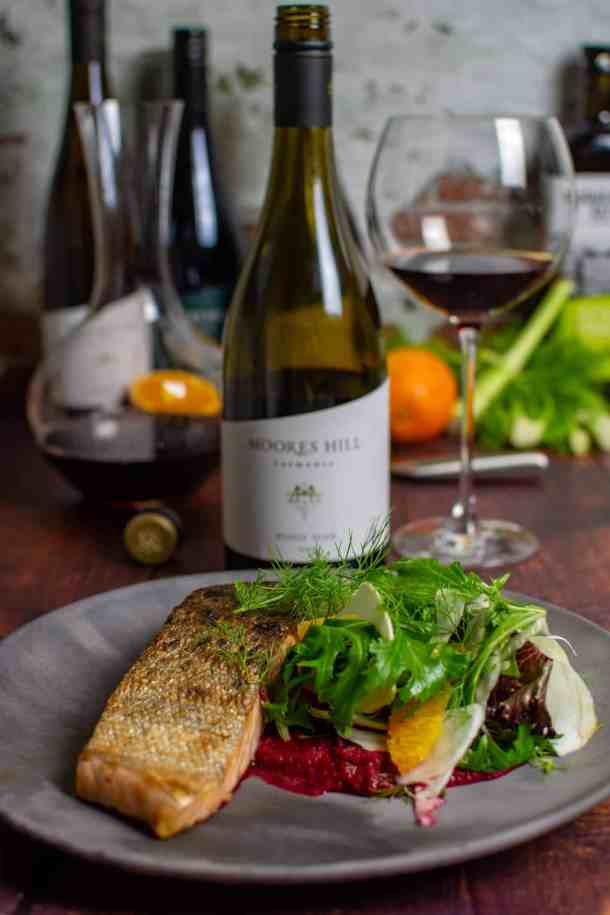 grilled salmon, beetroot hummus & fennel salad on a made of australia plate and a moores hill pinot noir in background