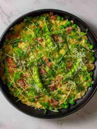 pea & baco risotto in a black bowl