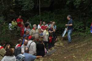 Franco Rasia illustra ad un gruppo di visitatori il rifugio che è proprio sotto i suoi piedi.