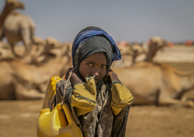 Una bimba trasporta una tanica di acqua © ANSA