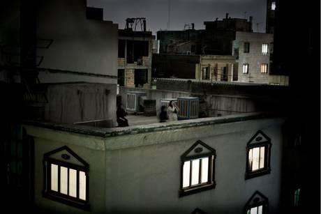 donna sul tetto di una casa, all'imbrunire, che urla