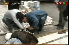 uno dei cristiani torturati e uccisi viene raccolto per strada