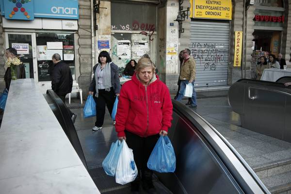 A woman carries bags of goods as she enters the metro station at the main Omonia square in Athens, Greece