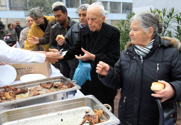 People wait in line for a free meal in Athens (archive)
